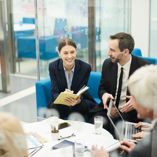 Group of cheerful business people discussing project sitting at coffe table during meeting, shot from behind glass, copy space