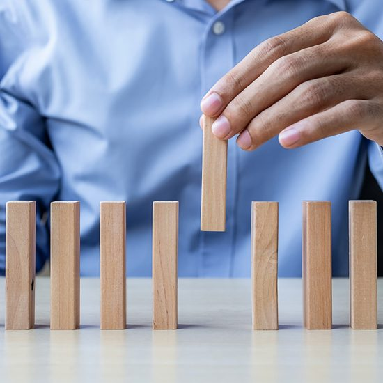 Businessman hand pulling or placing wooden Blocks or Dominoes. Business, Risk Management, Solution and strategy Concepts